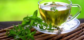 spearmint tea in a cup with spearmint leaves on the side